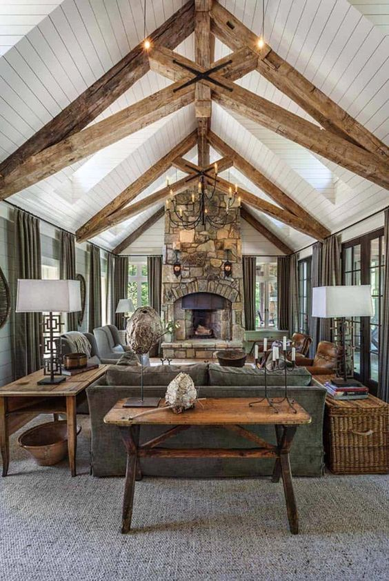 a welcoming barn living room with wooden beams, a fireplace clad with stone, grey seating furniture, a metal chandelier and baskets