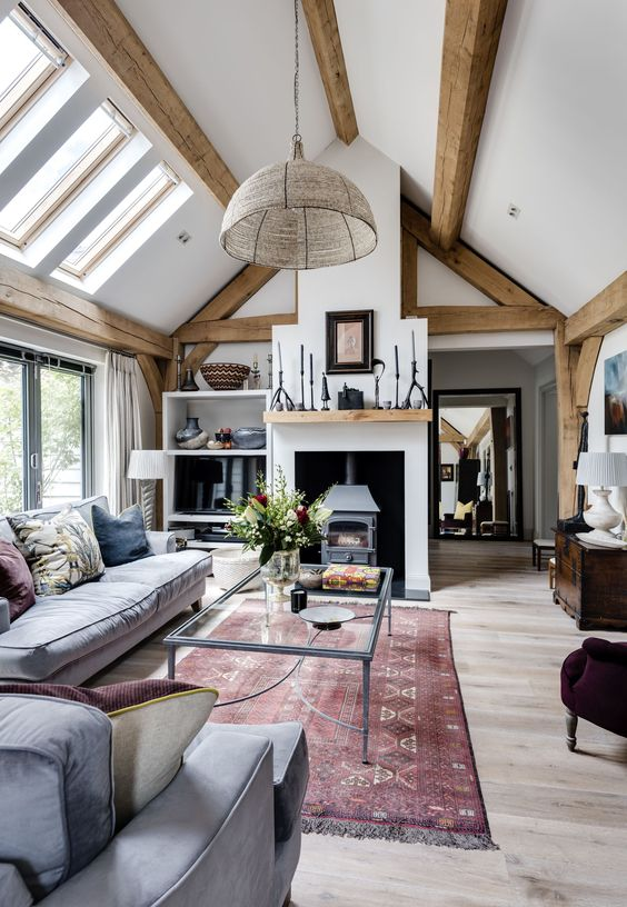 a welcoming barn living room with wooden beams,  a vintage hearth, grey seating furniture, a glass sofa, various accessories