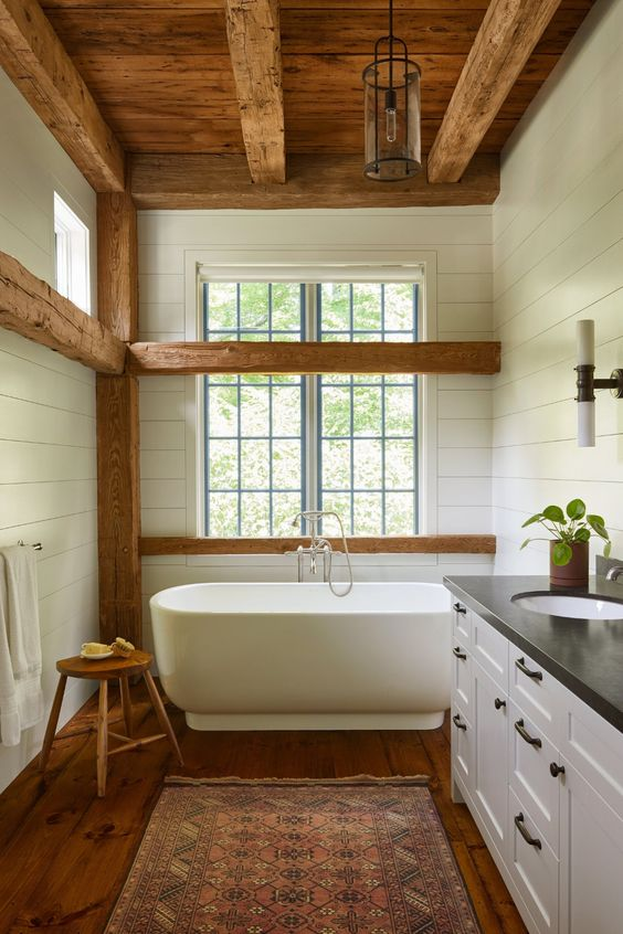 a white barn bathroom with wooden beams, a wooden ceiling with beams, a free-standing tub, vintage furniture