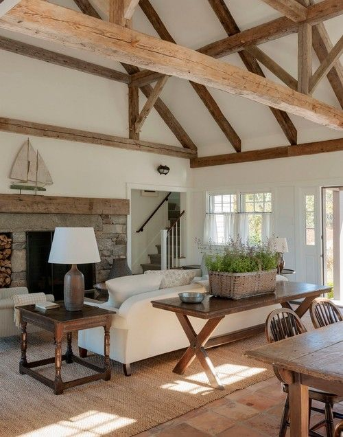 a white barn living room with a fireplace clad with stone, white seating furniture, dark stained tables, potted lavender in a basket and lots of wooden beams