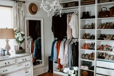 a white glam closet with open storage units and drawers, a shabby chic dresser, a large mirror, a crystal chandelier, a faux fur stool