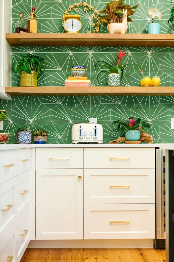a white shaker kitchen with white stone countertops and a bold green geo print backsplash, open shelves and potted blooms and plants