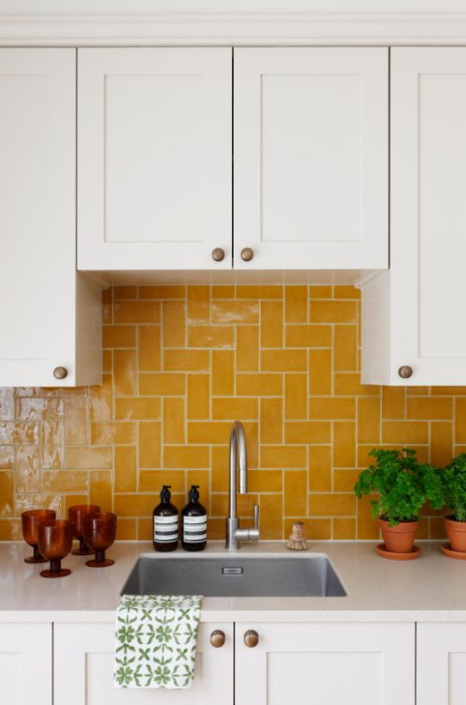 a white shaker style kitchen with a bold yellow tile backsplash that makes a color statement and creates a mood in the space
