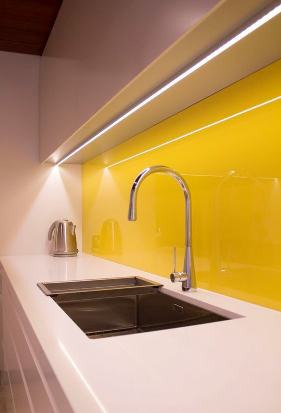 a white sleek kitchen with white countertops and a bold yellow glass backsplash that creates a mood and adds a sunny feel to the space