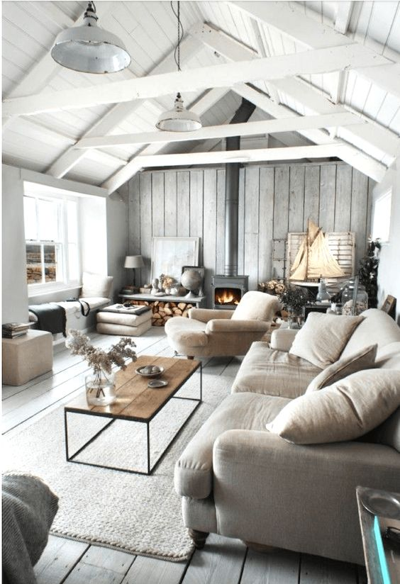 a whitewashed coastal barn living room with wooden beams, neutral seating furniture, a metal hearth, pillows and cushions
