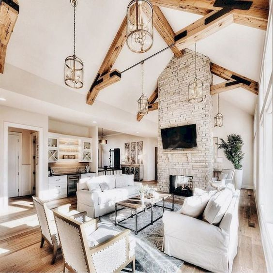 an airy barn living room with a brick fireplace, wooden beams, white seating furniture, a coffee table and lots of natural light incoming