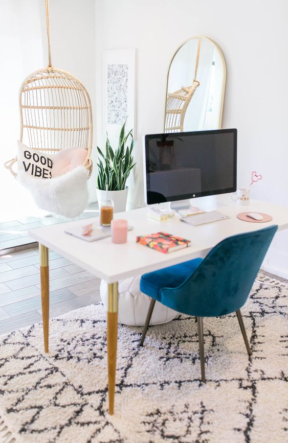 an airy feminine home office with a hanging rattan chair, a white desk, a navy chair and a statement mirror