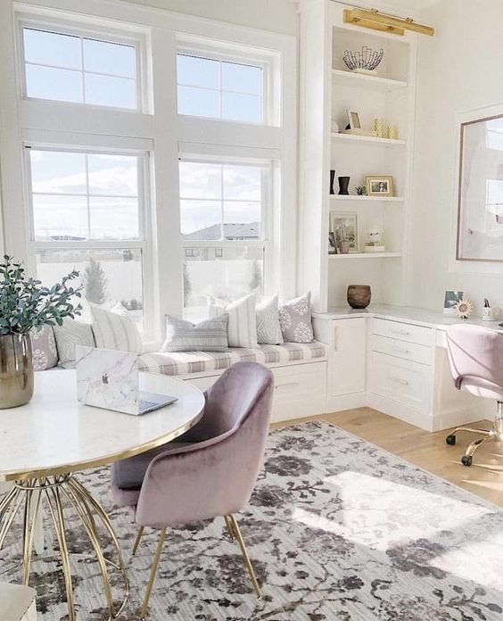 an airy neutral home office with lilac chairs, a printed rug, a windowsill daybed and storage units