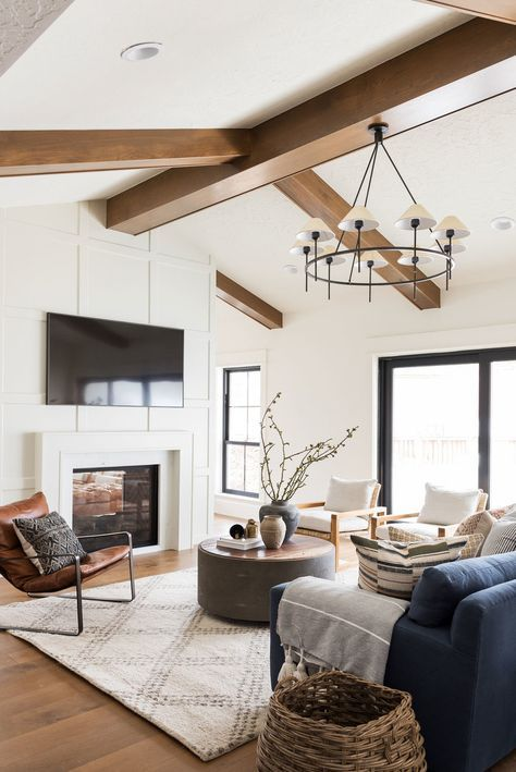 an elegant barn living room with a fireplace clad with panels, cool views, a navy sofa, white chairs, a round coffee table and baskets
