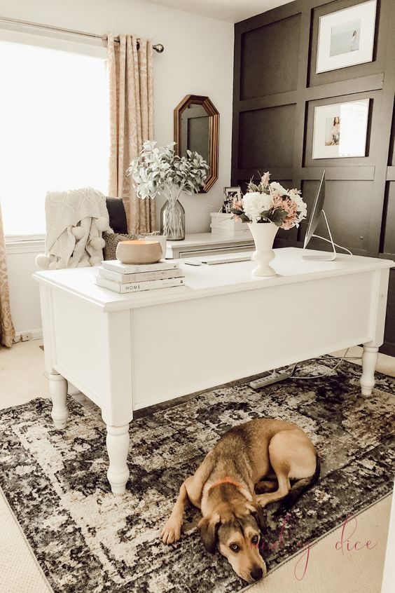 an elegant feminine home office with a black paneled wall, a white vintage desk, printed curtains and a rug and some blooms