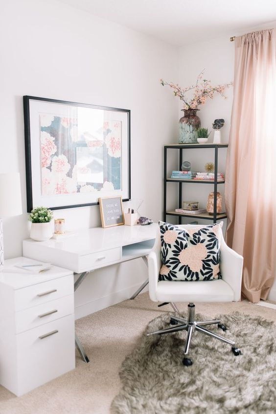 an ethereal home office with blush curtains, a floral artwork, a floral pillow and white furniture