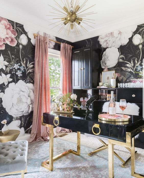 an exquisite feminine home office with floral walls, a black and gold desk, pink curtains and a gold burst chandeliers