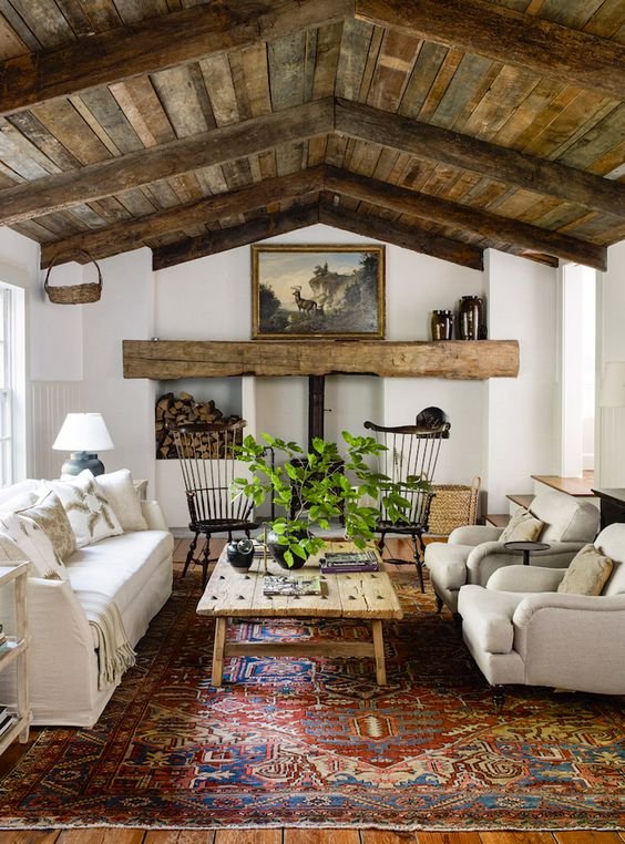an inviting barn living room with a metal hearth and a wooden mantel, a reclaimed wood ceiling, neutral seating furniture, a printed rug and greenery