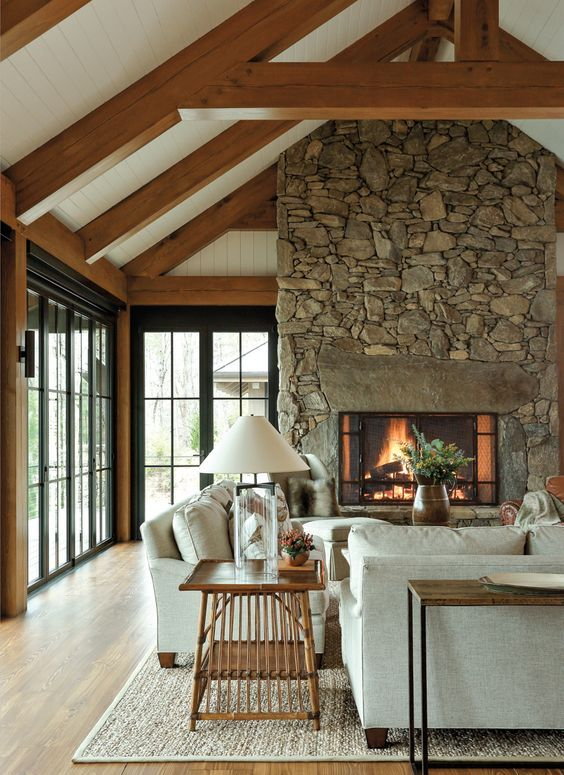 an inviting barn living room with wooden beams, a fireplace clad with stone, neutral seating furniture, wooden tables and some greenery
