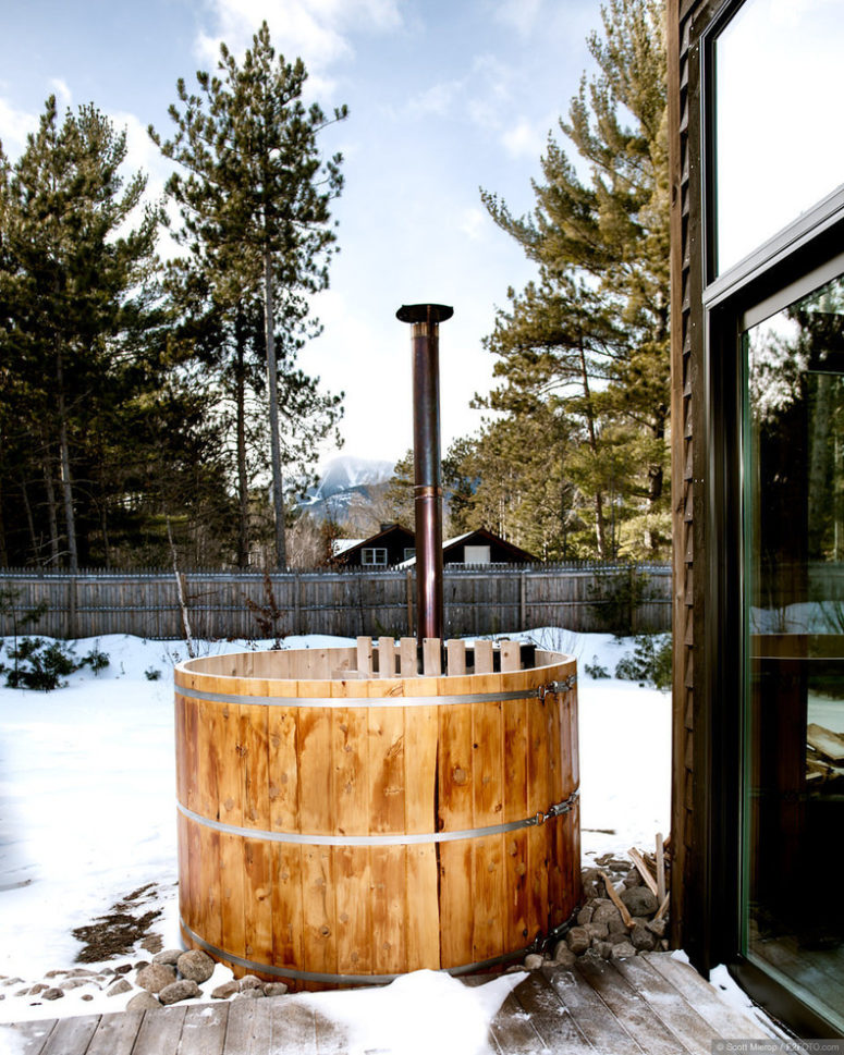 A small cedar hot tub on a deck is more than enough to enjoy view of mountains and woods around (Haas Habitats LLC)