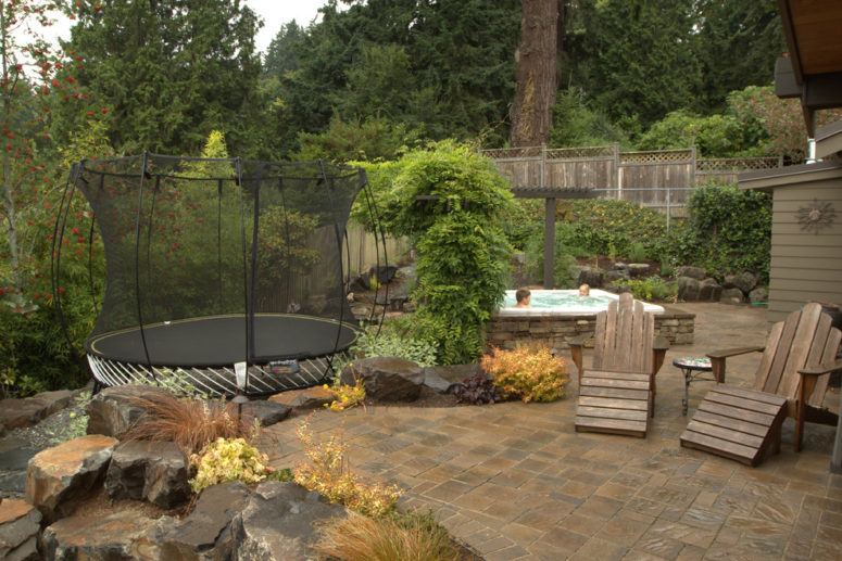 a built-in spa is a great way for adults to relax while kids are jumping on a trampoline (Alderwood Landscape Architecture and Construction)