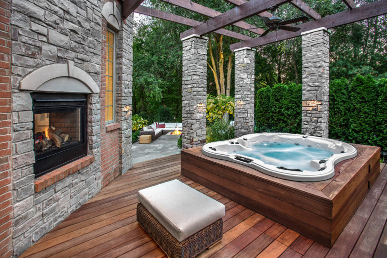 A fireplace and a spa bathtub is a perfect combination for a cozy patio. (Outdoor Living LLC)