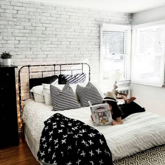 a Scandinavian bedroom with a faux white brick wall, a black metal bed and dresser, lights and monochromatic bedding