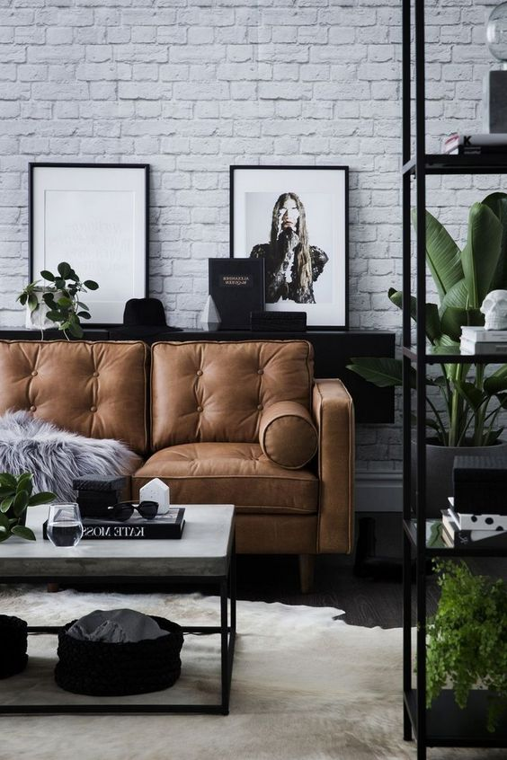 a Scandinavian living room in black and white, with a brown leather sofa and a white brick wall