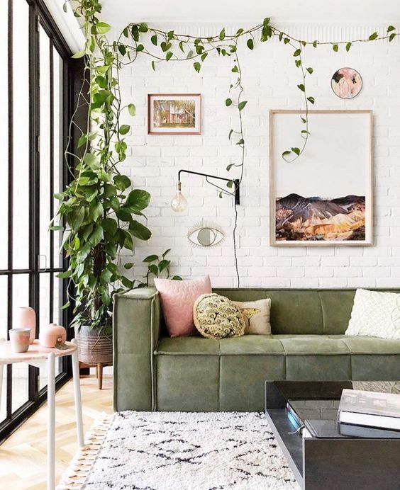 a boho chic living room with white brick walls, potted greenery, a green sofa and pink touches