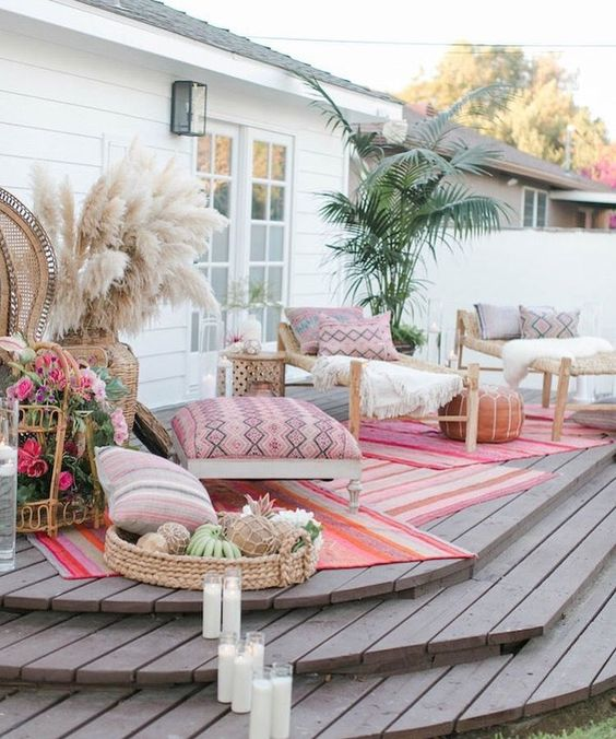 a boho deck with rattan furniture, pampas grass, greenery in a pot, candles and lots of floral arrangements