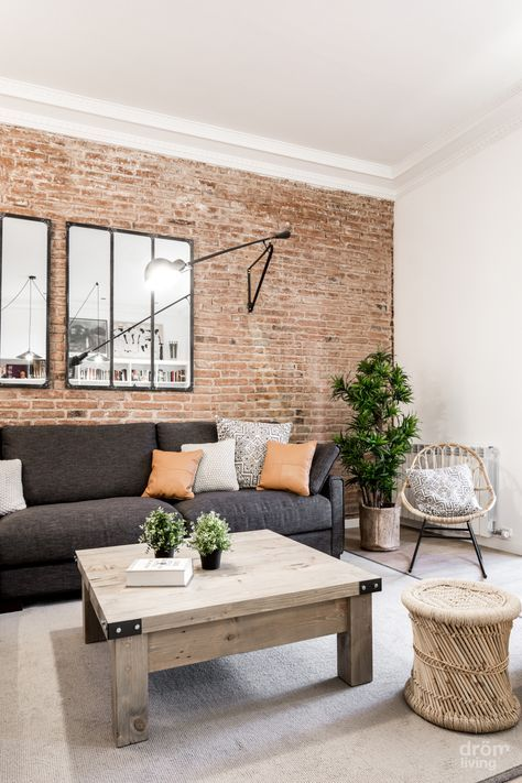a boho living room with a red brick wall, rattan and wood furniture and an upholstered sofa