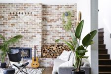 a boho living room with a whitewashed brick wall, potted greenery and neutral furniture