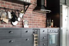 a bold kitchen with dark wooden cabinets and red brick walls for a catchy look with a vintage feel