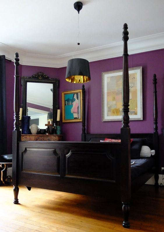 a bold purple bedroom with very dark furniture, a non-working fireplace and a mirror, a pendant lamp and bold artworks