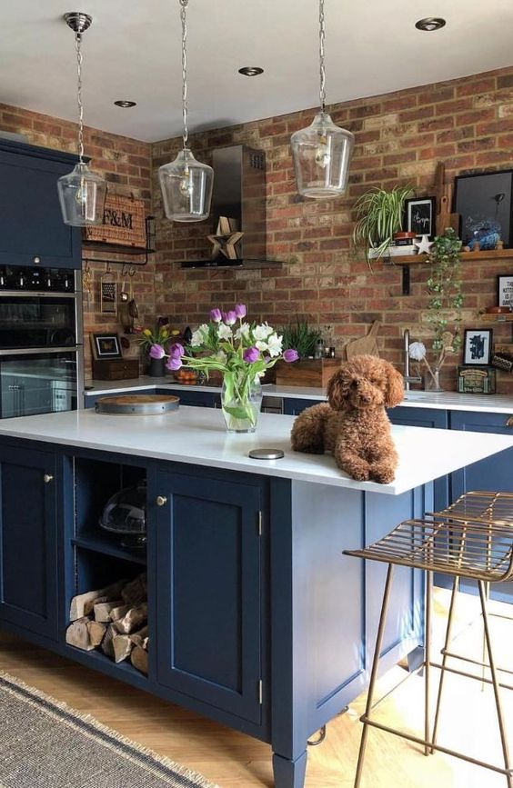 a bright blue kitchen with white countertops and glass pendant lamps is made bolder with red brick walls