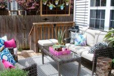 a bright boho deck with wicker furniture, planters with greenery and blooms, a bright blue chandelier and printed pillows