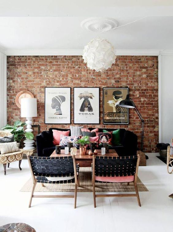 a bright boho living room with a red brick statement wall, black furniture and colorful pillows