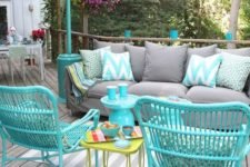 a bright deck with turquoise furniture, a grey sofa and printed pillows plus a printed rug for fun