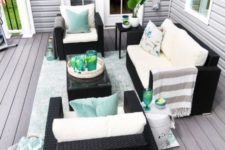 a bright summer deck with dark wicker furniture, neutral and light colored textiles and potted greenery is very welcoming