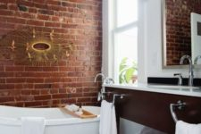 a chic bathroom done in white and with contrasting touches – a red brick wall and a rich toned vanity