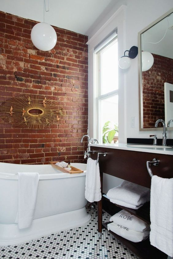 a chic bathroom done in white and with contrasting touches - a red brick wall and a rich toned vanity
