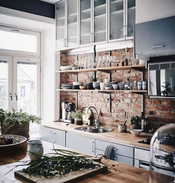 a chic kitchen with blue cabinets, light colored countertops and a red brick wall looks very refreshing