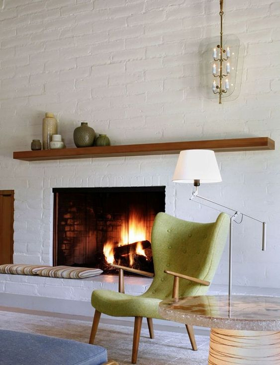 a chic mid-century modern living room done with white brick walls and green accents
