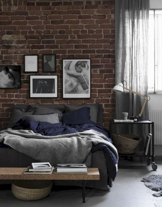 a chic moody bedroom with a faux brick wall, a cork bench, a dark bed and a monochromatic gallery wall
