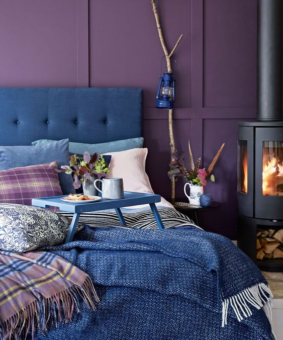 a colorful bedroom with deep purple panel walls, a blue bed and blue bedding, a hearth and a lamp on a branch