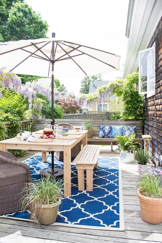a colorful deck with a printed rug, wooden furniture, potted greenery and blooms plus an umbrella