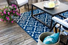 a colorful eclectic deck with a bright rug, wicker and wooden furniture, colorful textiles and bright blooms in planters