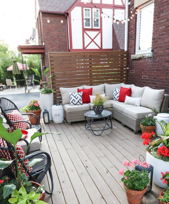 a colorful summer deck with a sectional sofa, potted greenery and blooms, rattan chairs and lanterns
