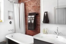 a contemporary bathroom with a red brick touch that makes it more industrial and more eye-catchy