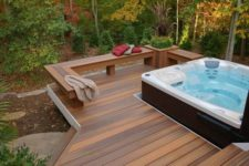 a contemporary deck with a built-in bench with a planter and a large jacuzzi plus a view to the forest