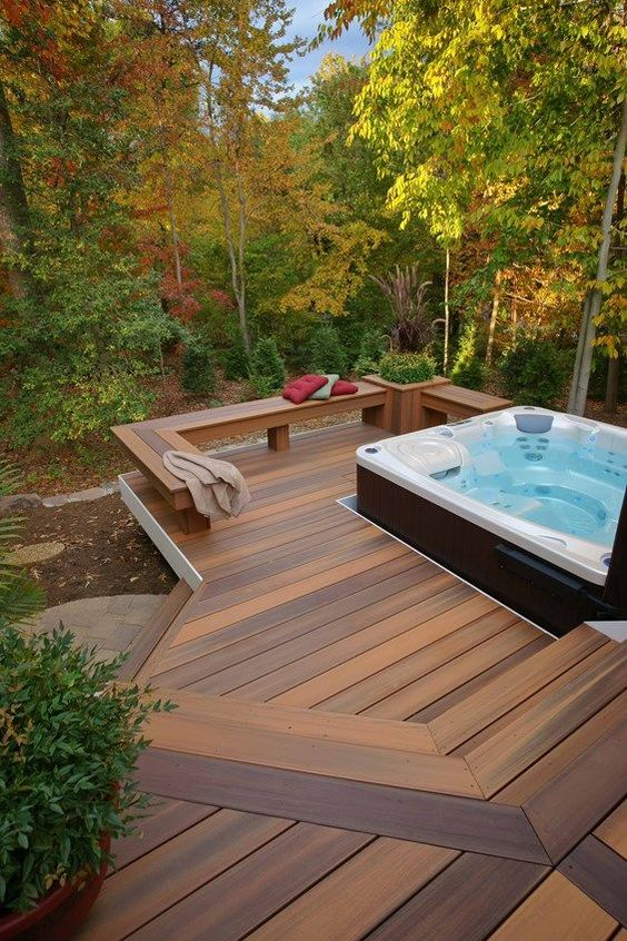 a contemporary deck with a built in bench with a planter and a large jacuzzi plus a view to the forest