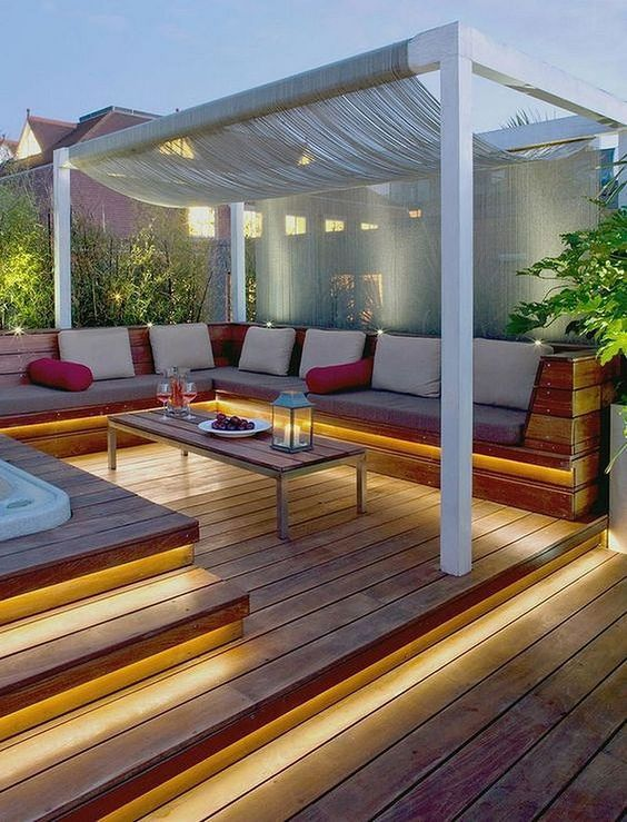 a contemporary deck with built-in lights in the steps and a built-in bench, a coffee table and a canopy over the sitting zone