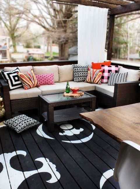 a contrasting deck with a black and white floor, dark wicker furniture and colorful pillows