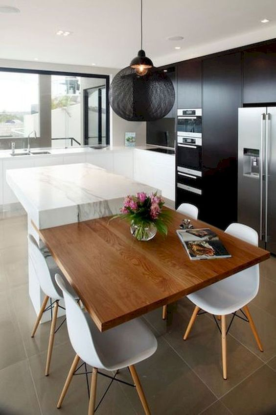 a contrasting kitchen island of white stone and a plywood table is a bold additional to monochromatic kitchen
