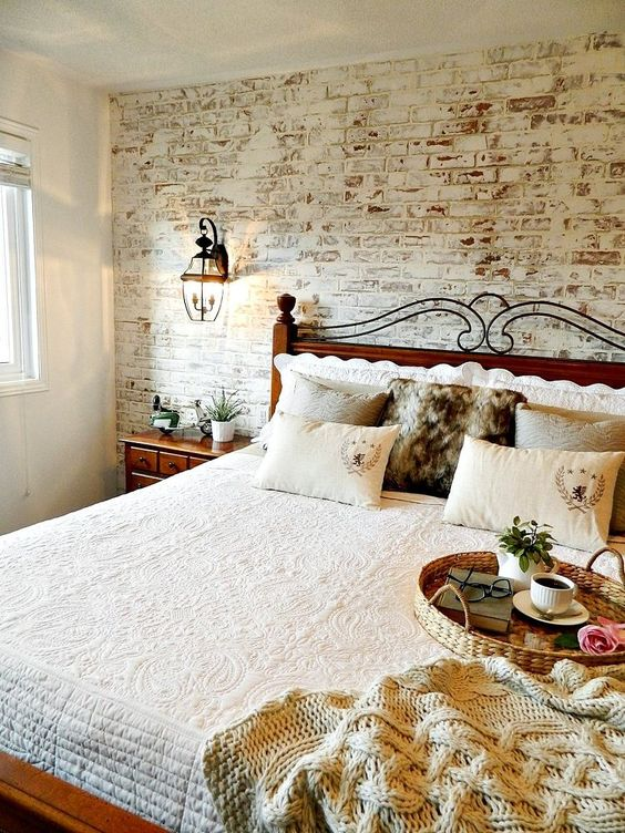 a cozy rustic space with a fake whitewashed brick wall and rich stained furniture that contrasts it